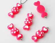 Synthetic pendants/charms candy decorated with hearts and with metal eye ± 26x10mm