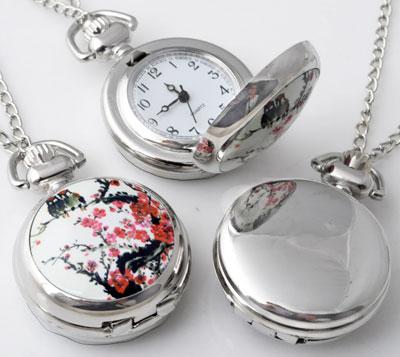 www.beadyourfashion.nl - Metalen halsketting ± 77cm met klokje/horloge versierd met keramiek met bloesem ± 43x29mm